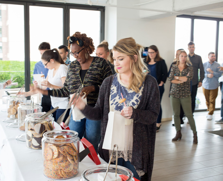 Agency employees enjoy milk and cookie shots while selecting various cookies for their cookie bag at the Twentieth Television Milk & Cookie Bar.